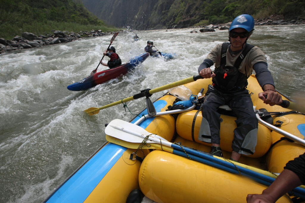 Amazon Express expedition raft guide Juan Antonio de Ugarte of Cuzco, Peru guides the raft through rapids on the lower Rio Mantaro as white water kayakers follow. From back left, Daniel Rondon Casos (red and blue kayak), Santiago Iba–ez Corpancho, and expedition leader West Hansen (far back).  Amazon Express expedition in Peru September 21, 2012.   Photo by Erich Schlegel
