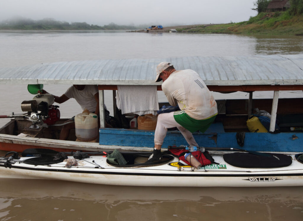 Amazon Express expedition member Pete Binion gingerly climbs into his kayak for departure from Flor de Punga on the Ucayali River in Peru. Binion's feet were suffering from jungle rot and he was trying to keep the as dry as possible so they could heal. Binion dropped out of the expedition in Iquitos due to health problems and scheduling with work back home.  Amazon Express expedition in Peru October 15, 2012.   Photo by Erich Schlegel