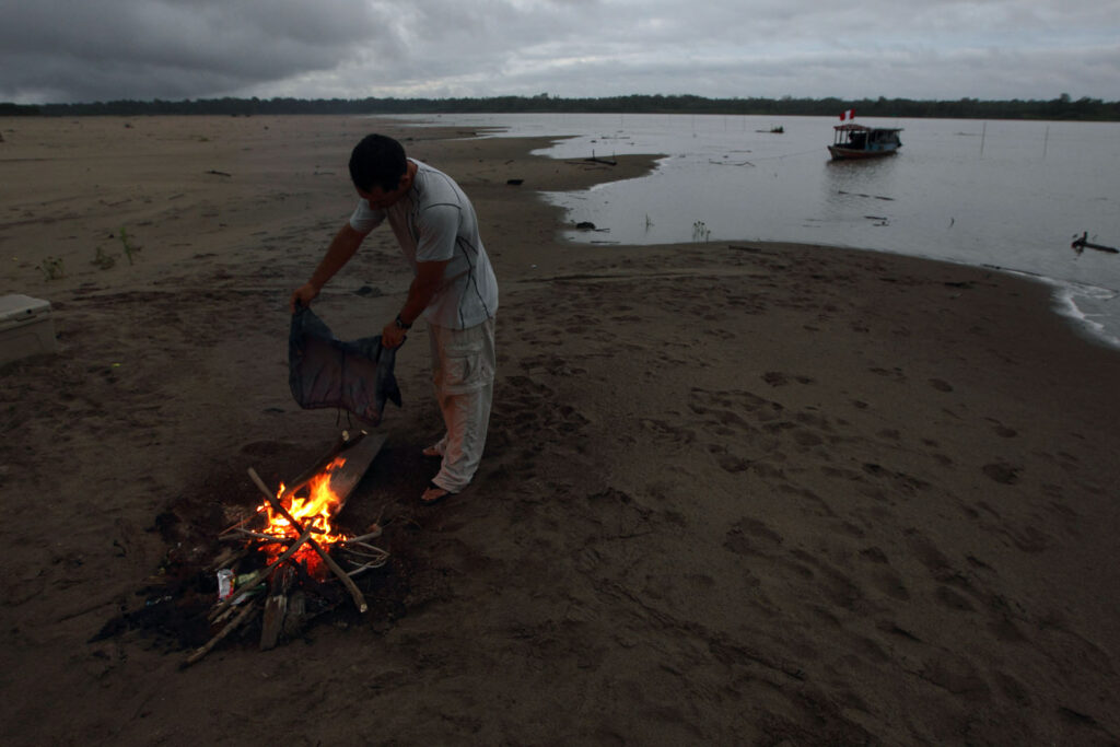 The Amazon Express expedition member Ian Rolls dries his short over the campfire at dawn at a sand beach camp on the Ucayali River in Peru.   Amazon Express expedition in Peru October 16, 2012.   Photo by Erich Schlegel