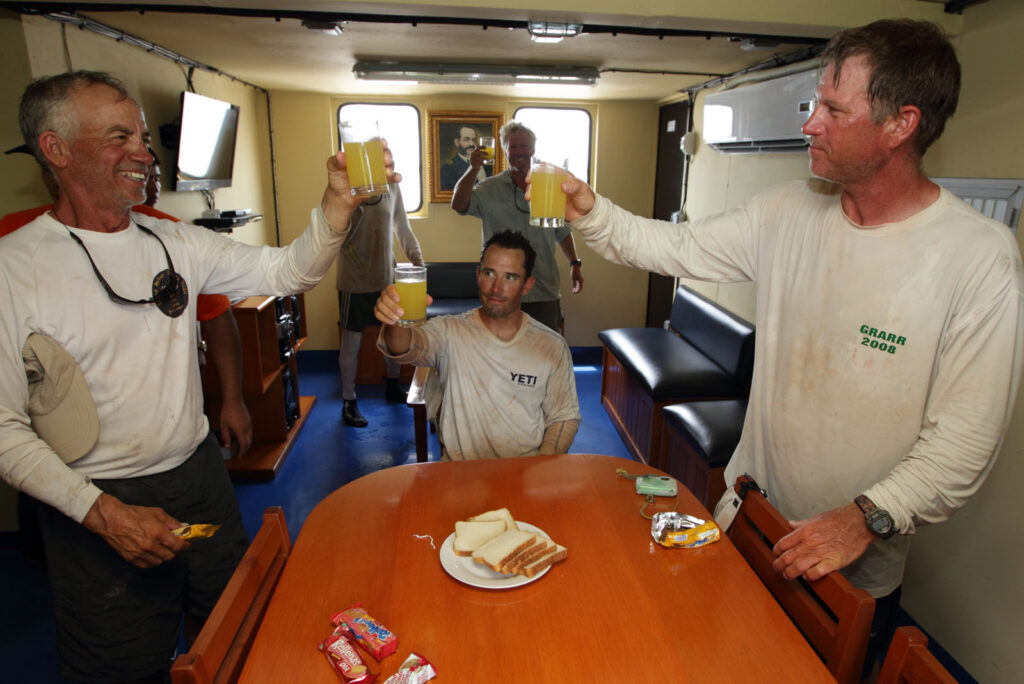 "Amazon Express expedition members, from left, Jeff Wueste, Ian Rolls, Jason Jones, and West Hansen toast with ice hold fruit juice aboard the Peruvian Navy vessel ""Stiglich"" on the Ucayali River in Peru. The Peruvian Navy and Coast Guard provided a security escort through various sections of the Ucayali River where pirates were known to prey on boats. They were invited to spend their lunch break aboard the vessel in air conditioned comfort..  Amazon Express expedition in Peru October 17, 2012.   Photo by Erich Schlegel"