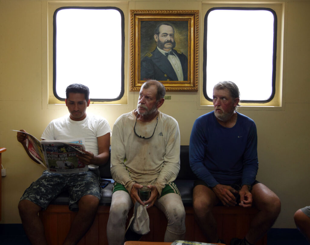 "From left, guide Cesar Pe–a, Amazon Express expedition members Pete Binion and John Maika rest aboard the Peruvian Navy vessel ""Stiglich"" on the Ucayali River in Peru. The Peruvian Navy and Coast Guard provided a security escort through various sections of the Ucayali River where pirates were known to prey on boats. They were invited to spend their lunch break aboard the vessel in air conditioned comfort. Above the group is a portrait of Peruvian Navy admiral Miguel Grau, hero of the war with Chile.  Amazon Express expedition in Peru October 17, 2012.   Photo by Erich Schlegel"