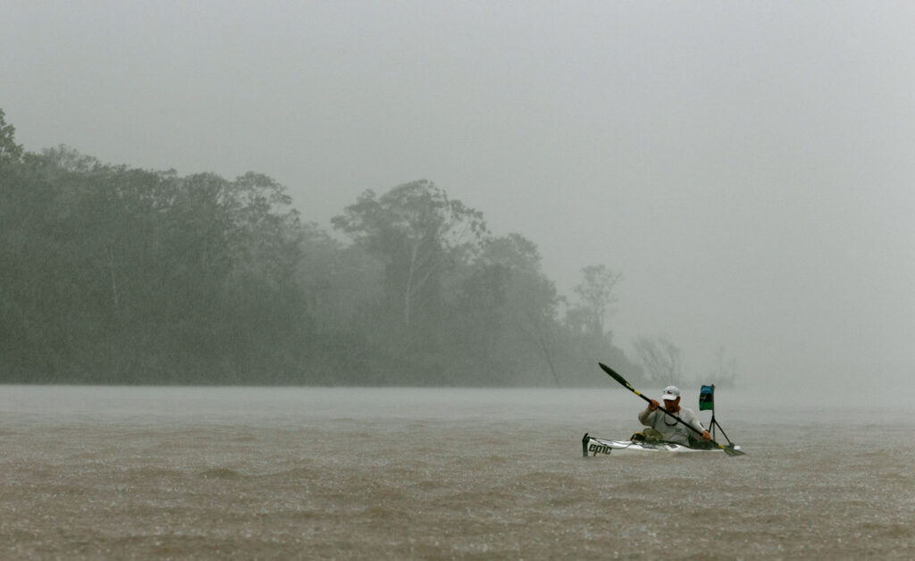 Amazon Express expedition leader West Hansen paddles during a heavy rainstorm on the Ucayali River as the team approaches Iquitos, Peru.   Amazon Express expedition in Peru October 17, 2012.   Photo by Erich Schlegel