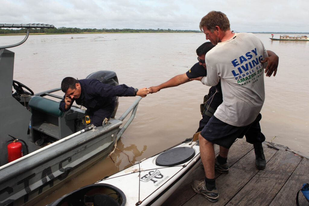 Amazon Express expedition leader West Hansen, far right, hangs onto Peruvian Navy boat driver Aroni as he hangs onto Peruvian Navy ensign Emilio Huaco on a boat dock in Tamshiyacu on the Ucayali River in Peru. The Peruvian Coast Guard escorted the Amazon Express expedition through the final phase going into Iquitos, Peru.  Amazon Express expedition in Peru October 18, 2012.   Photo by Erich Schlegel