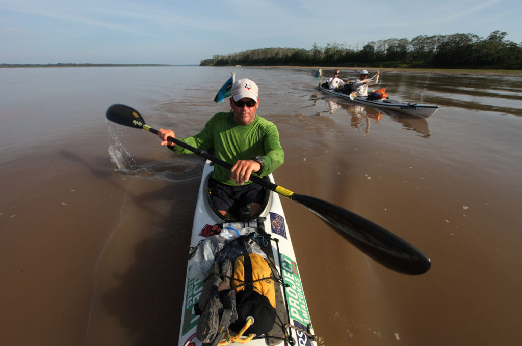 Amazon Express expedition leader West Hansen, left, paddles his solo kayak as team members Jeff Wueste and Ian Rolls paddle their tandem kayak after leaving the campsite on Isla de Loreto on the Colombian side of the Amazon River. This was the team's final push through Peru to the Brazilian border.  Amazon Express expedition October 27, 2012.   Photo by Erich Schlegel
