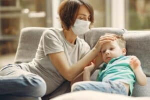 A mother, wearing a mask checking her young son's forehead for a fever.