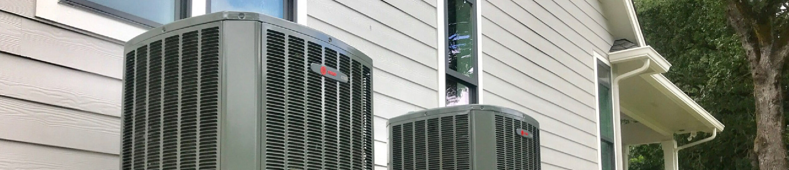 Two external Air Conditioners units outside of a home