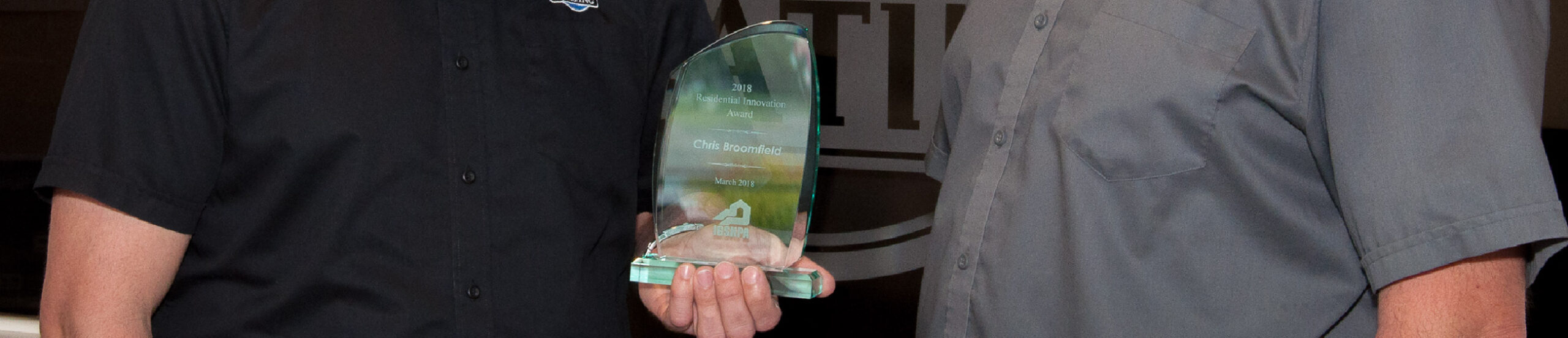 Close up of a glass award being held by two men