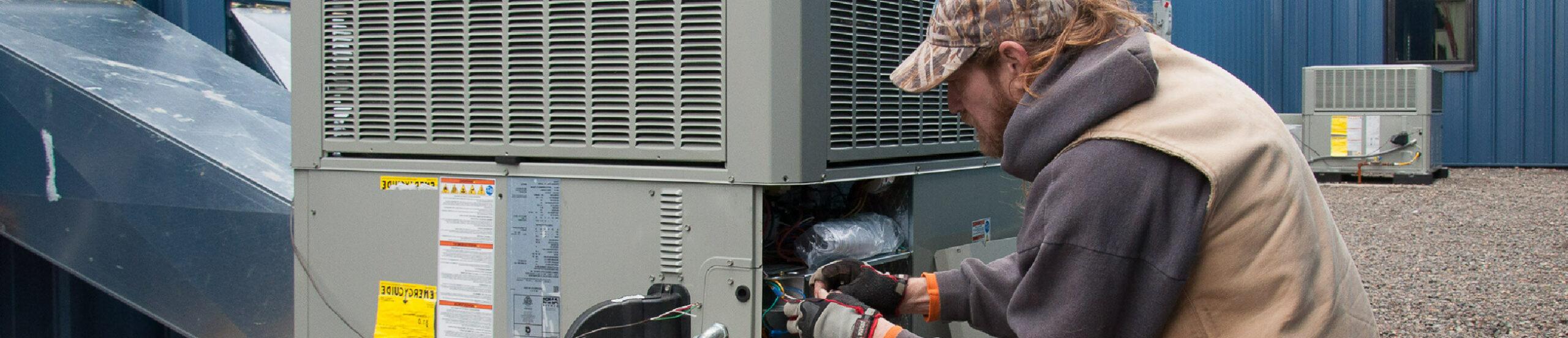 HVAC technician servicing a commercial HVAC unit