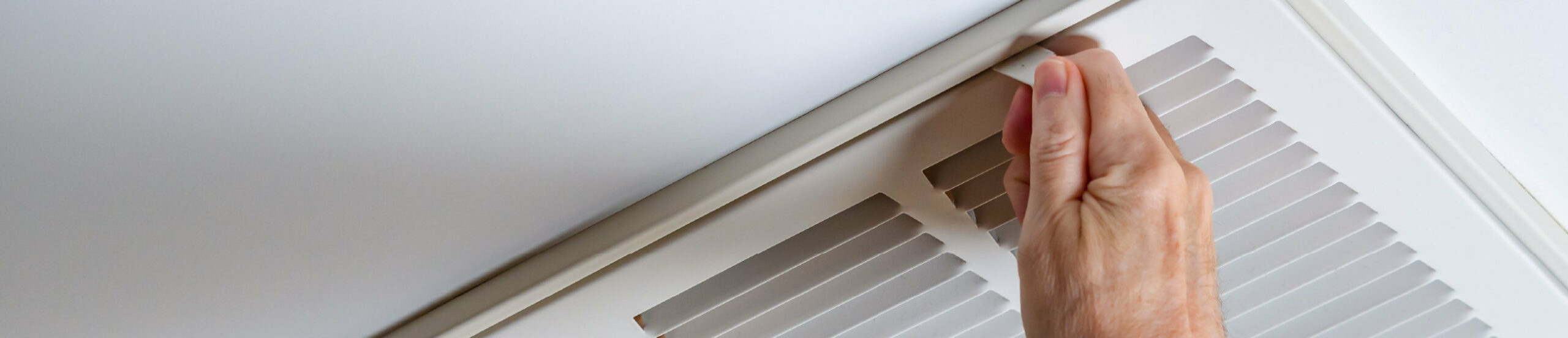 Close up of an air duct, with a hand adjusting the vent guards