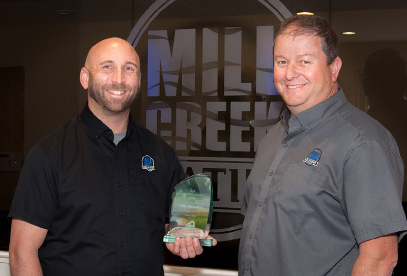 Two men wearing Mill Creek Heating shirts and standing in front of a large Mill Creek Heating sign. Man on left is holding an award.
