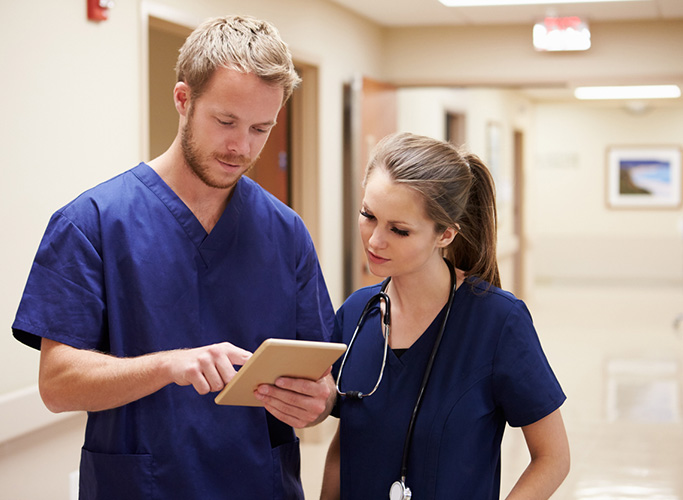 Medical Staff Looking At Digital Tablet In Hospital Corridor