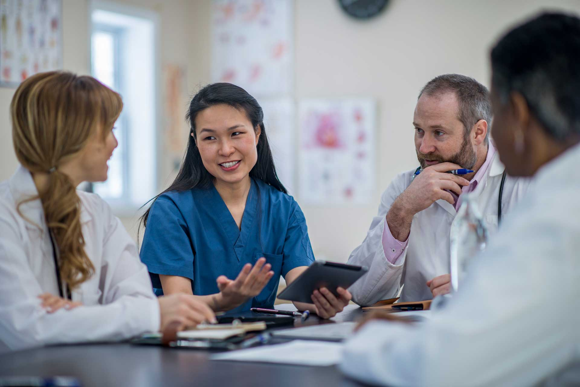 a group of doctors and nurses having a discussion using sentact digital platform