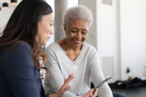 doctor talking to an elderly patient while holding a tablet using sentact technology