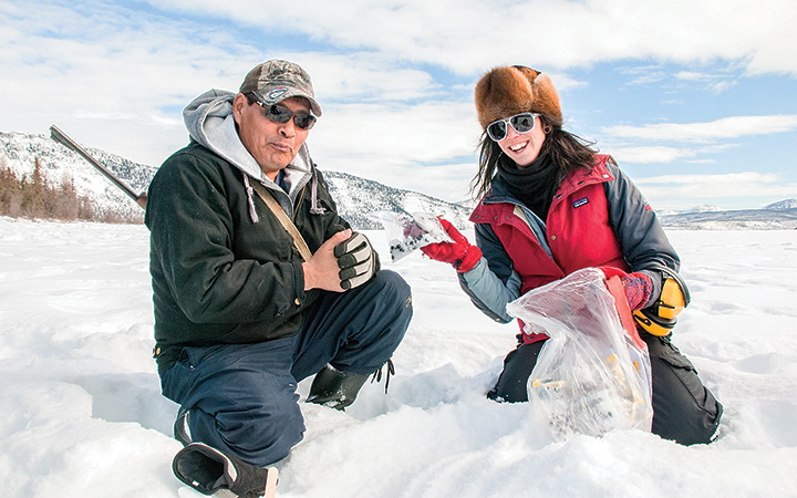 Student John Tobac and instructor Genevieve Coté collect caribou scat samples on Drum Lake.