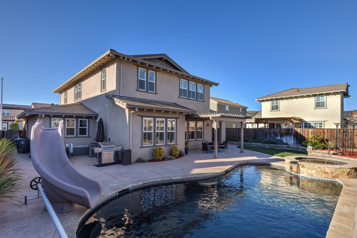 Backyard with pool, slide, and spa at 1550 Bautista Way, Morgan Hill - Terra Mia at Mission Ranch