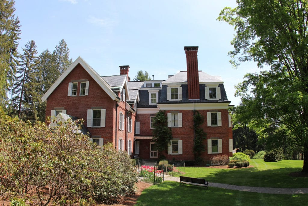 A red brick house with three stories and a chimmney