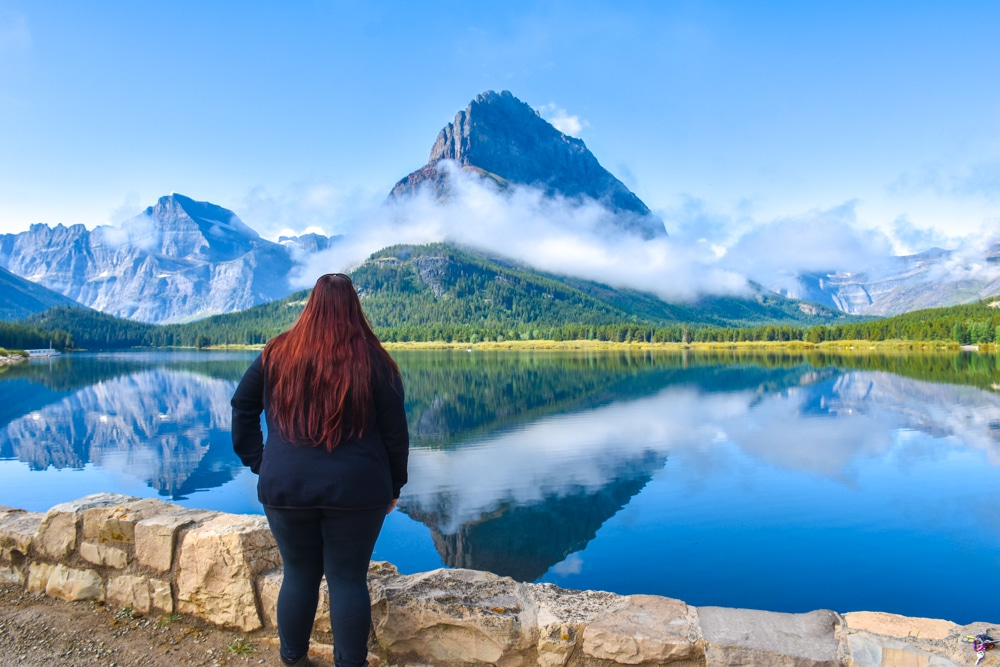Woman standing next to a mountain partially hidden by clouds reflected by a lake in Many Glacier, Glacier National Park