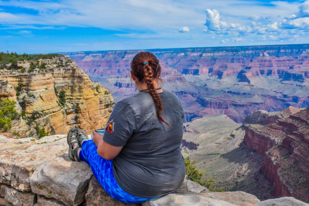 A women sitting down enjoying the view of the Grand Canyon.