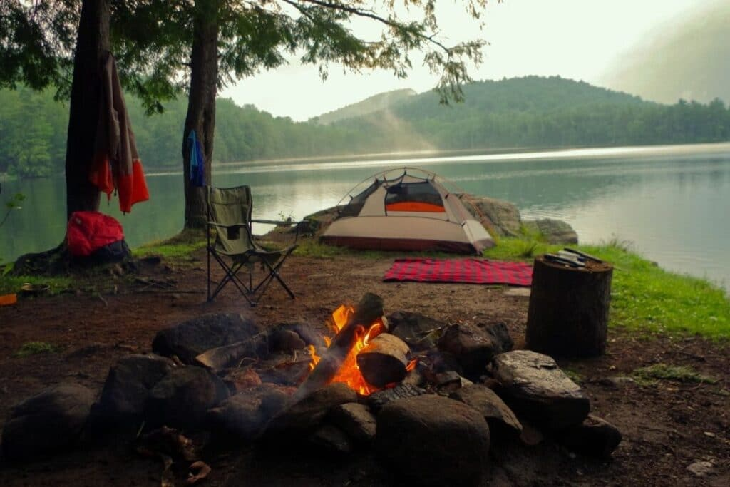 Campsite by the lake with a tent and campfire.