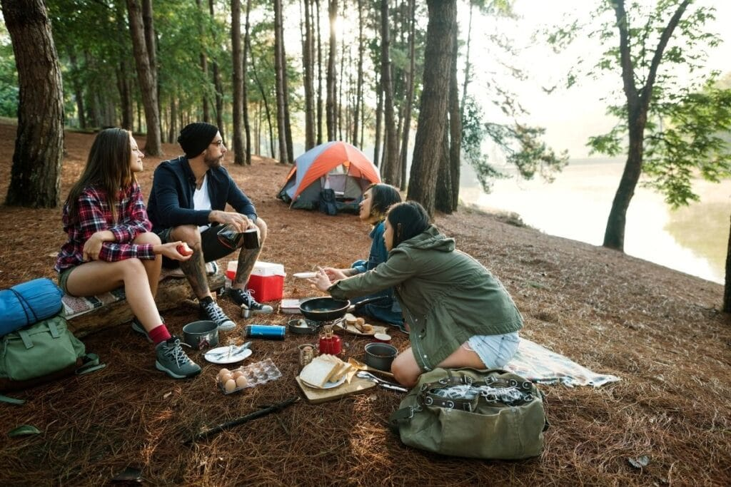3 women and a man having breakfast while camping by a lake.