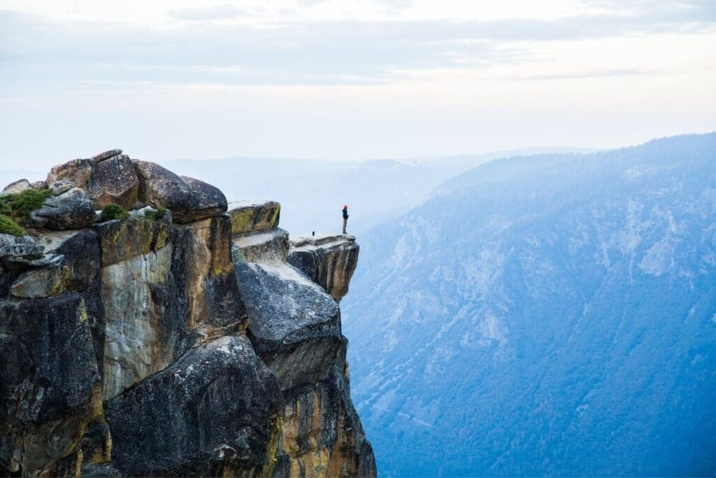 A man enjoying the a view while standing on a rock outcropping