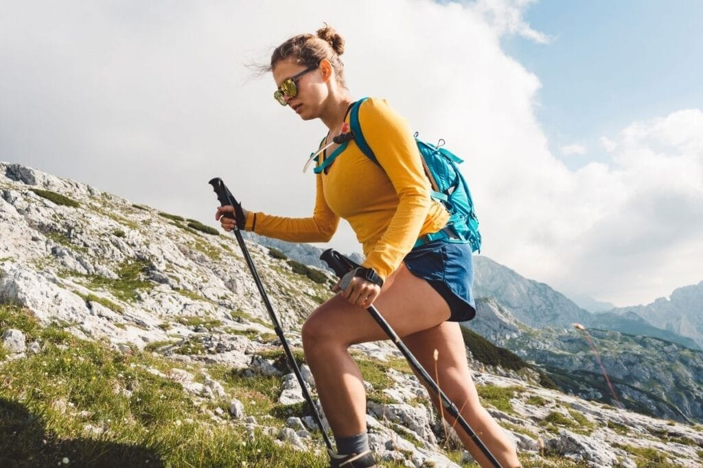 A women in a yellow shirt and trekking poles hiking up an incline