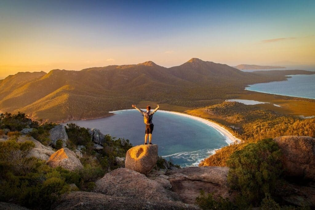 A man standing with his arms raised enjoying the view of the mountains and a bay.