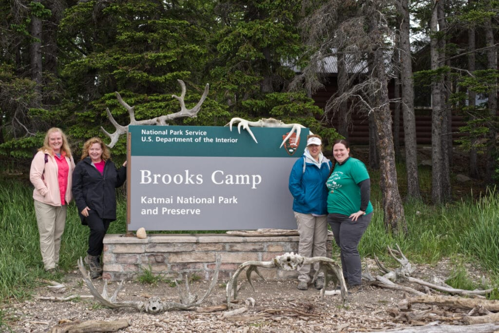 Four women standing with the Brooks Camp Sign.