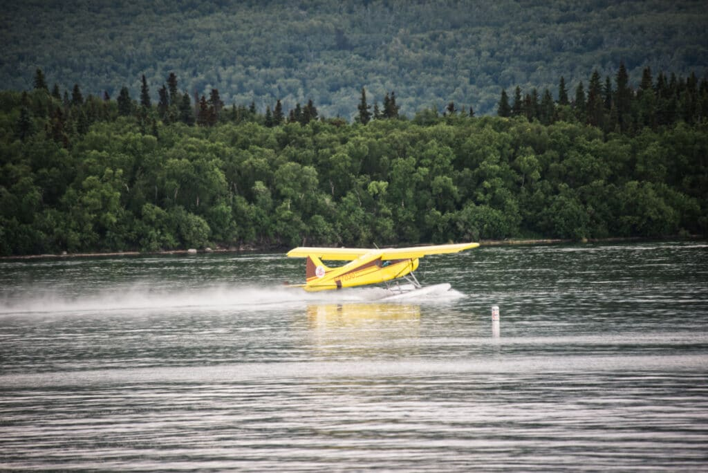 A yellow float plane preparing for take-off at Brooks Camp