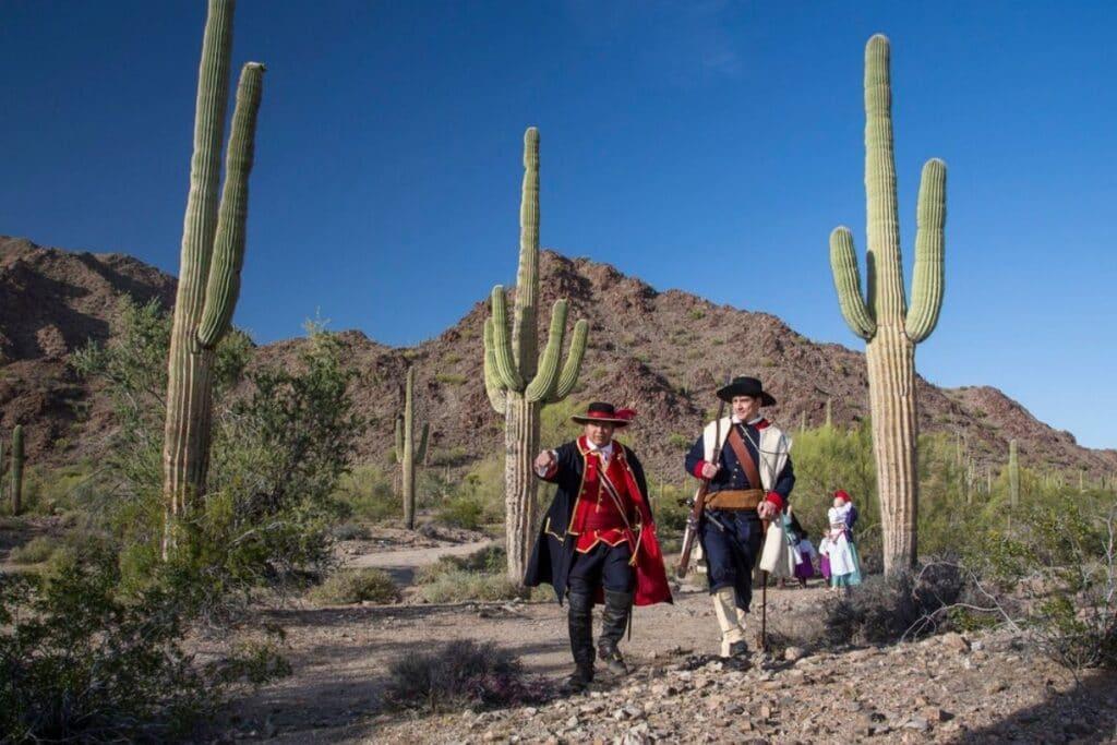 People in a period costume walk next to some saquaro.