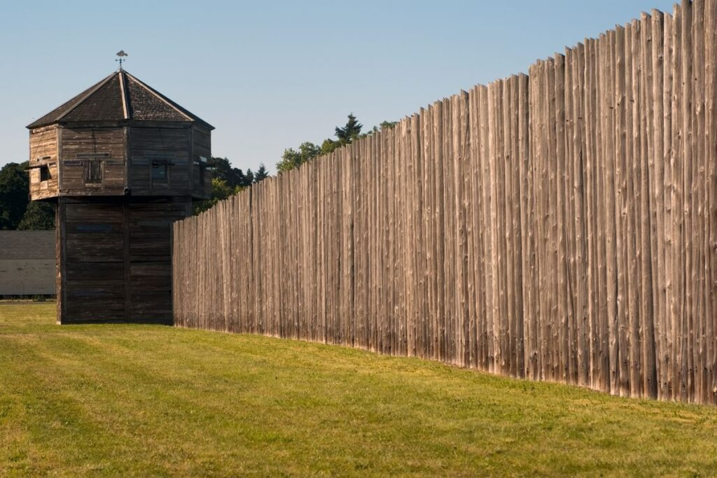 A wooden palisade wall with a tower
