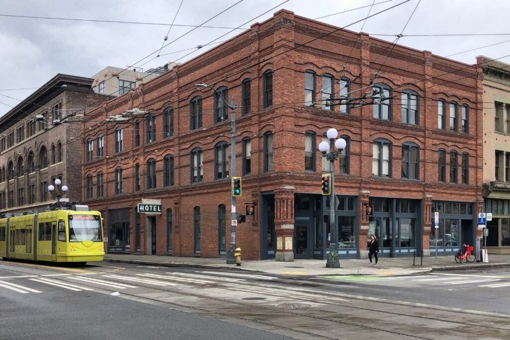 A brick building with a yellow tram in front