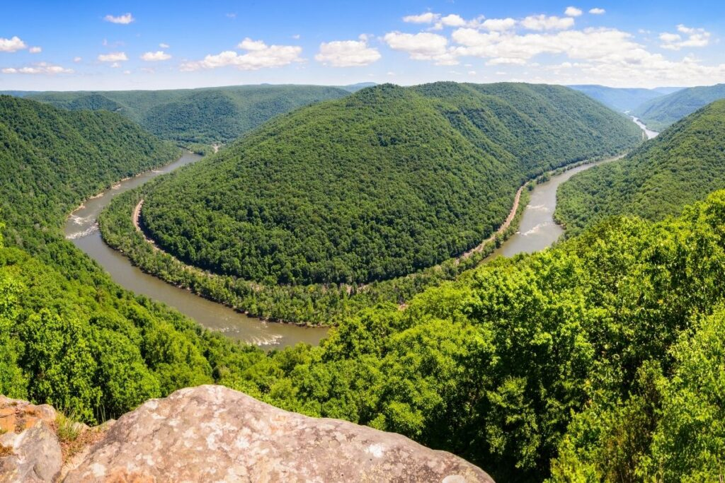 Standing on a rock looking down on a green valley with a horseshoe river bend.