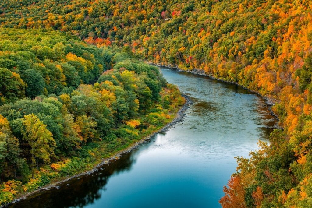 A river bend with fall colors in the trees.