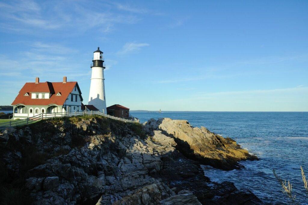 A white lighthouse on a rocky shoreline