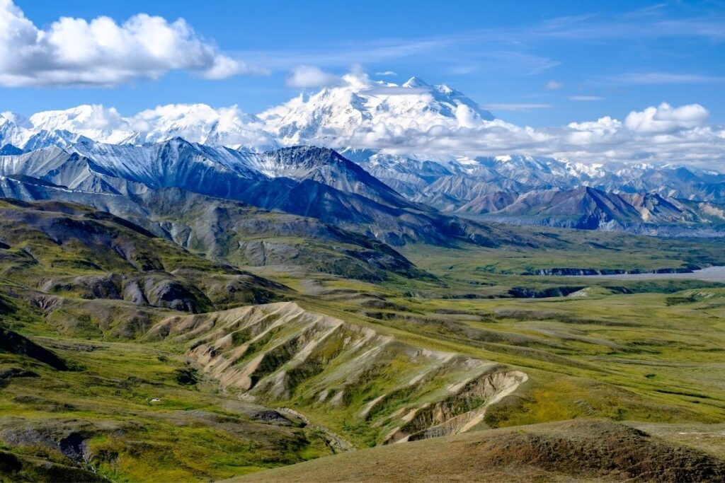 The green valleys in front of Denali which is partly hidden by the clouds.