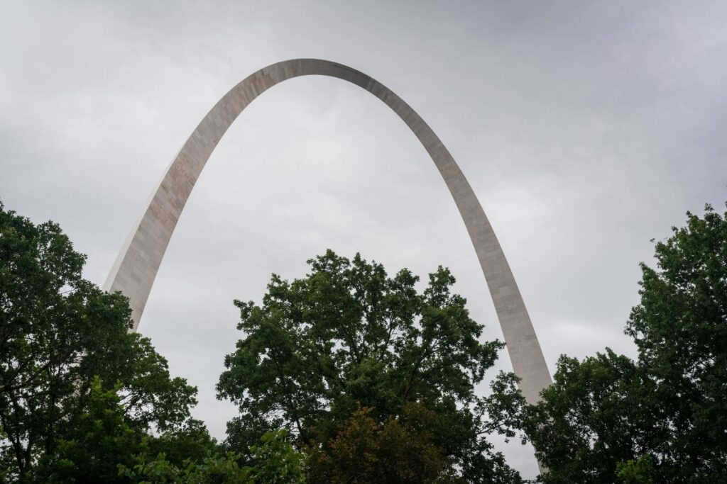 A concrete arch with a few trees in front