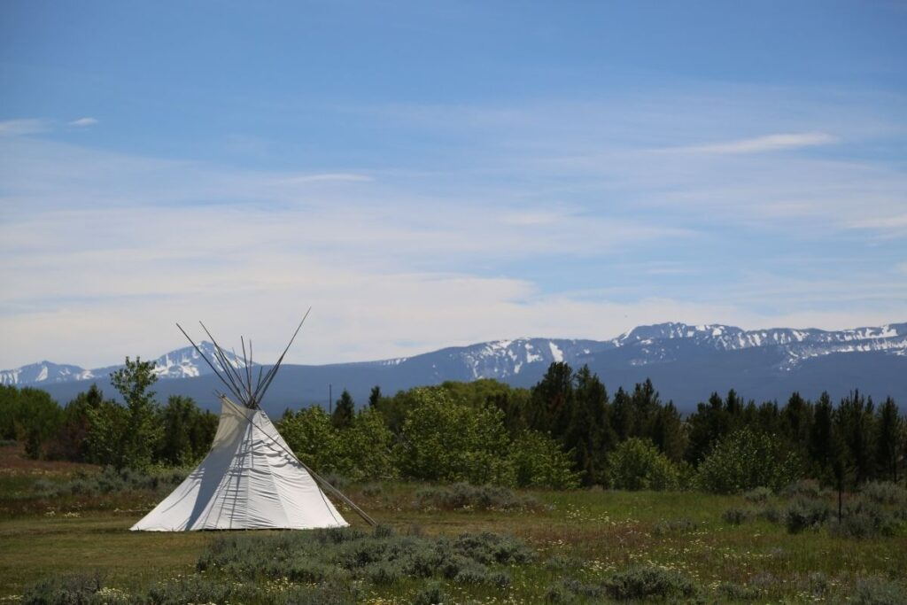 A teepee with mountains in the background.