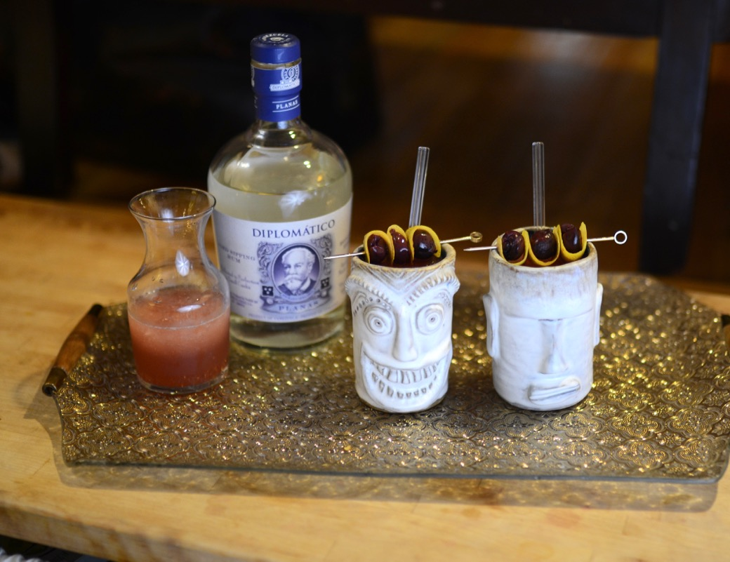 two handmade tiki mugs on a gold tray with a bottle of diplomatico white rum