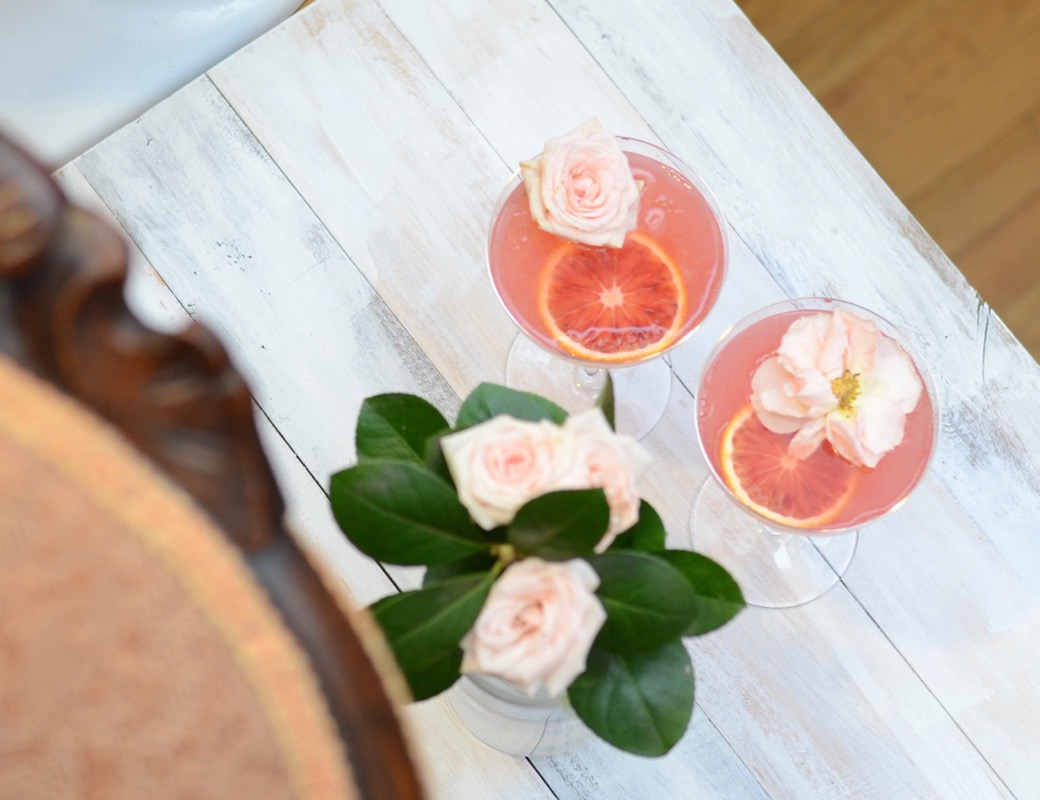 two coupe glasses with margaritas and rose garnishes