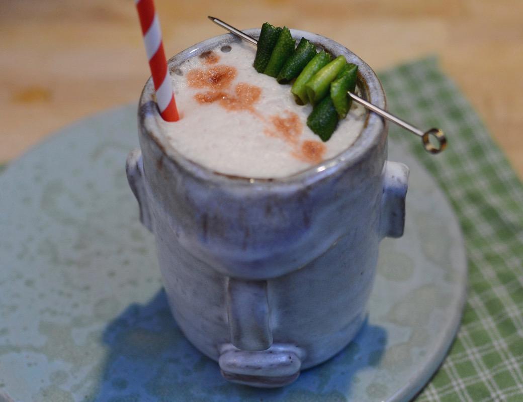 cocktail with a lime garnish in a handmade tiki mug
