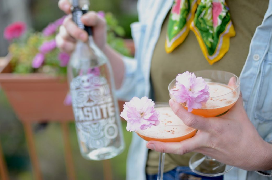 bottle of tequila with two coupe glasses and cherry blossoms for garnish