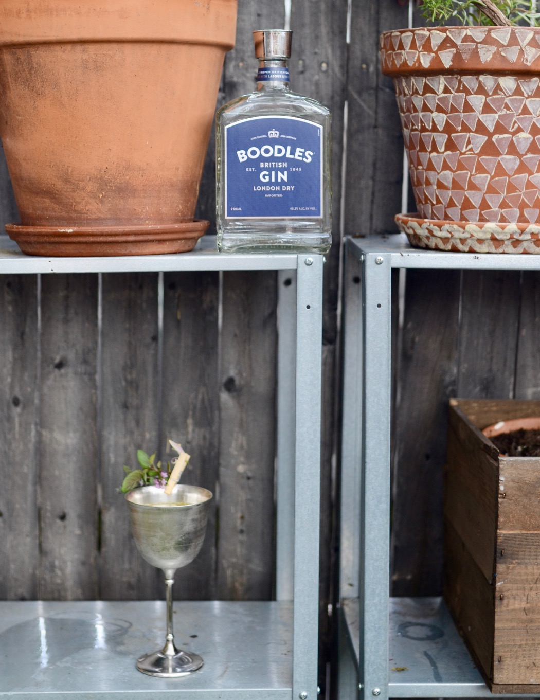 boodles gin bottle with a cocktail in a silver goblet outside