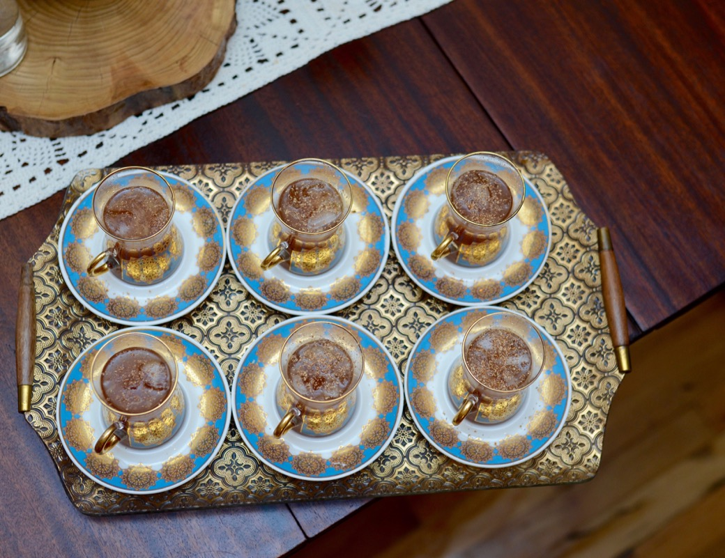 6 Turkish tea cups on a gold tray with a cocktail