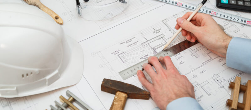 Image of engineer or architectural project, Close up of engineer's hand drawing plan on BluePrint with Engineering tools on workplace.