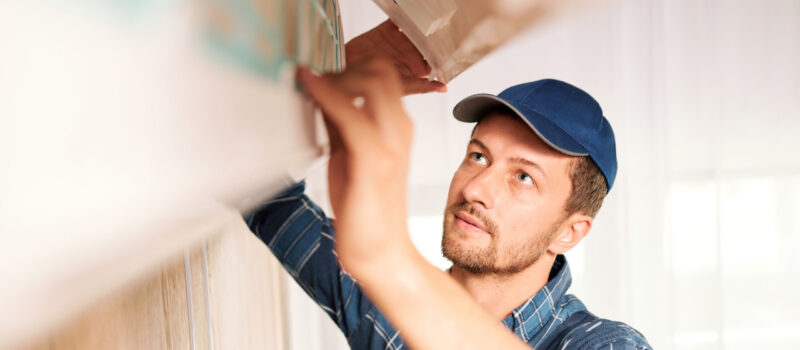 Young workman in workwear looking into system of air conditioner to find out reason of disorder