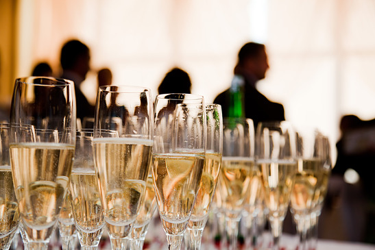 Image: Table of full champagne glasses with people in background