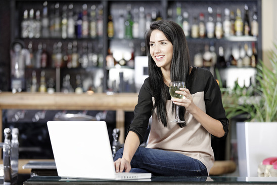 Image: Woman Drinking Wine in Bar on Laptop