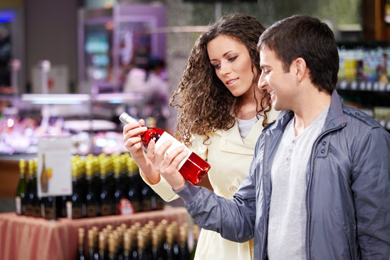 Image: Couple Looking at Bottle of Wine in Shop