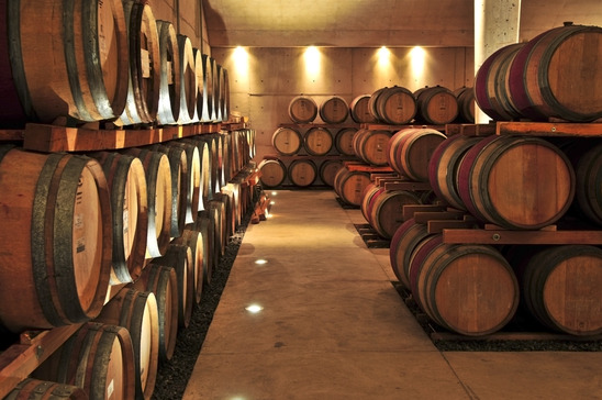 Image: Stacked oak wine barrels in winery cellar